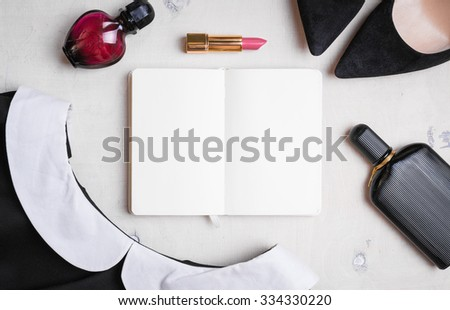 Blank notepad with feminine objects. Black dress with white collar, shoes, lipstick, perfumes. Feminine cosmetic background. Get ready for work - stock photo