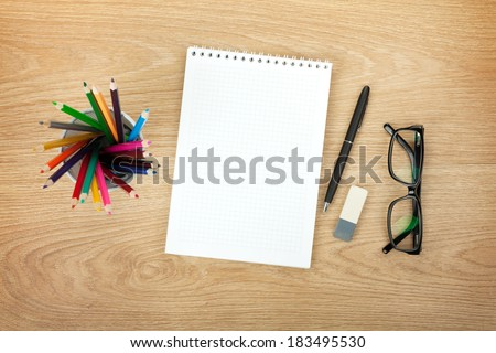 Blank notepad with office supplies and glasses on wooden table. Above view - stock photo