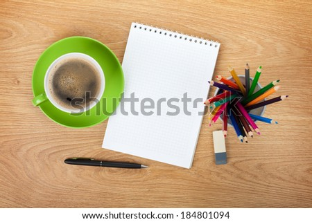 Blank notepad with office supplies and green coffee cup on wooden table. Above view - stock photo