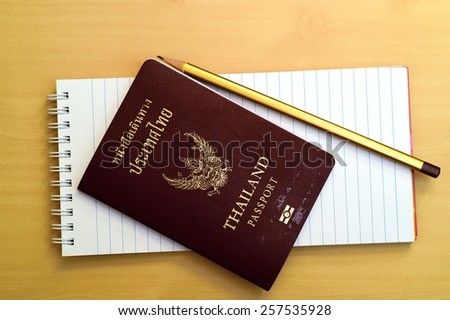 Blank notepad with passport of Thai on wooden table. Above view. - stock photo