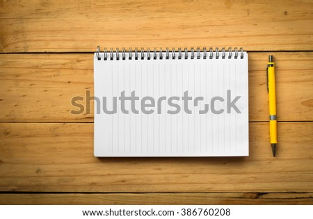 Blank notepad with pen or pencil on office wooden table in warm tone - stock photo