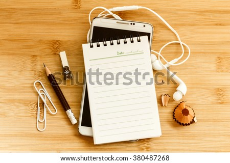 Blank notepad with  pencil and smart phone on wooden table , overhead shot or Top view - stock photo