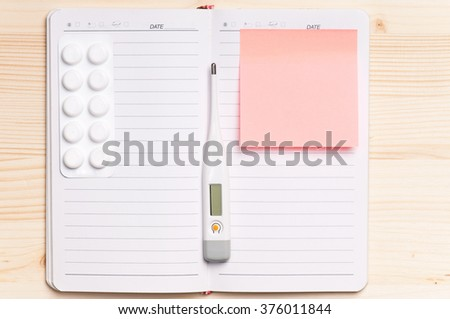 Blank notepad with thermometer on the wooden table. View from above - stock photo