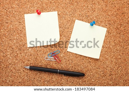 Blank notes on cork notice board with pen - stock photo