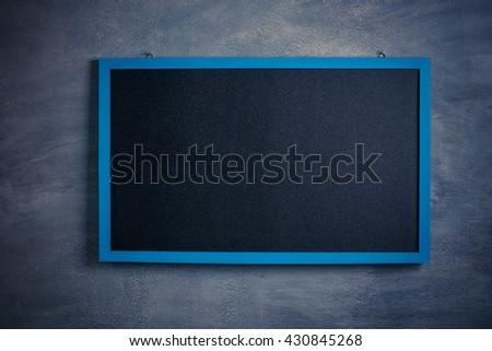 Blank old blackboard on cement background - stock photo