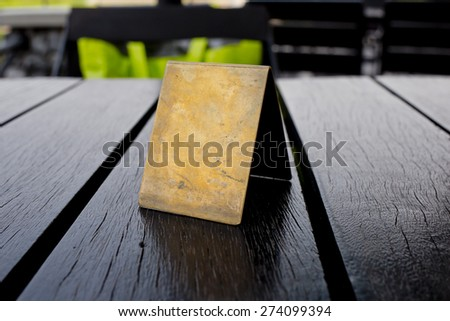 Blank old brown leather table card on wood table. - stock photo