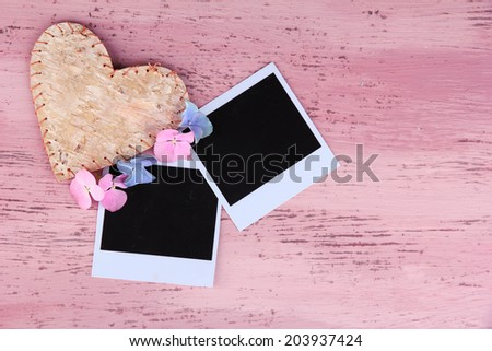 Blank old photos and decorative heart on color wooden background - stock photo