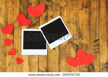 Blank old photos and decorative hearts on color wooden background - stock photo