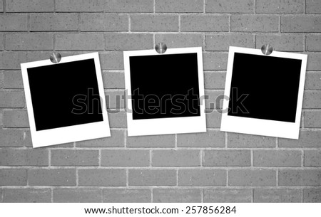 Blank old photos on clips on brick wall background - stock photo