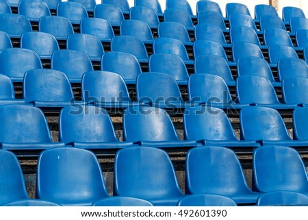 Blank old plastic chairs at the stadium. Number of empty seats in a small old stadium. Scratched worn plastic seats for fans