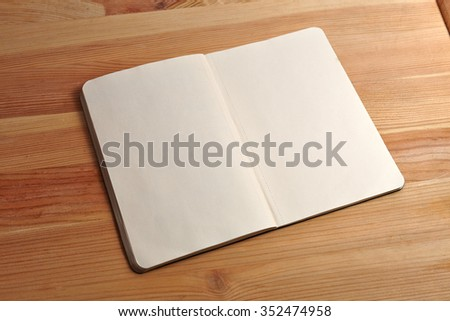 Blank open book isolated on wood background. Front view. Paper texture. Mock up. - stock photo