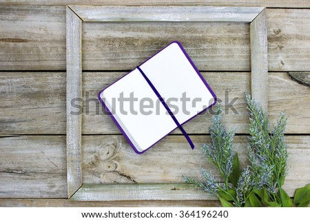 Blank open book with purple ribbon in rustic wooden frame with flower border - stock photo