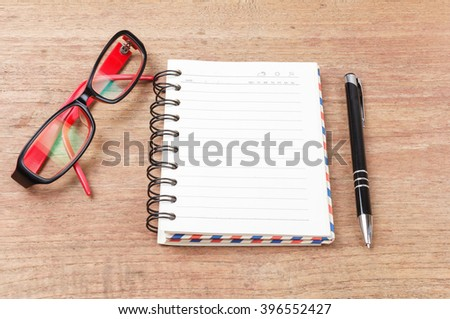 Blank open notebook with pen and glasses on wood table,Business template mock up for adding your text