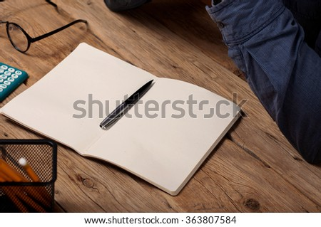 Blank open notepad with a pen on a wooden office desk closeup - stock photo