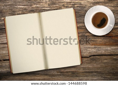 Blank opened book and cup of coffee on wooden table