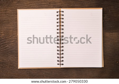 Blank opened note book on wood table.