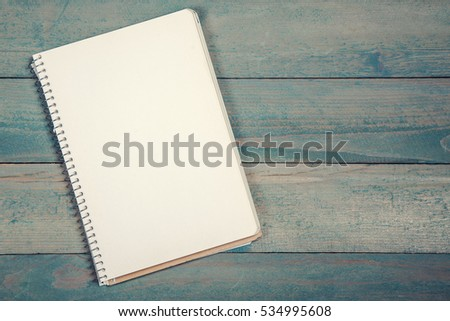 Blank opened notebook on wooden background