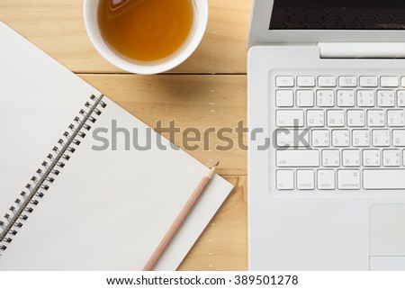 Blank opened notebook with cup of tea on wooden desk
