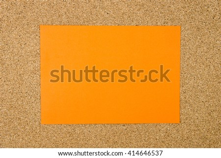 Blank orange paper note over cork board background, copy space available