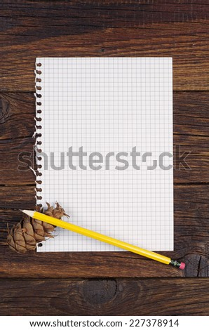 Blank page from a notebook, pencil and pine cone on old wooden table. Top view