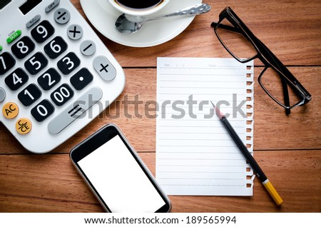 Blank Page notebook and calculator on the wooden desk background - stock photo