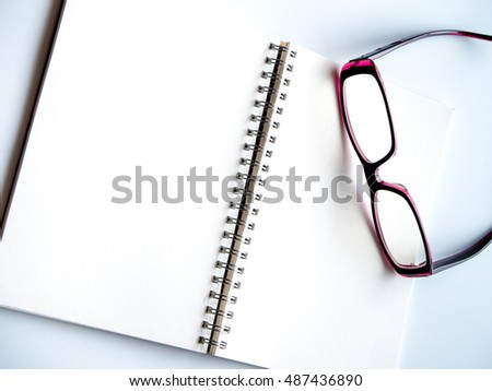 Blank page of a spiral notebook and eyeglasses