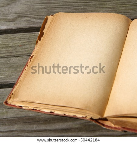 Blank page of an old book on wooden background