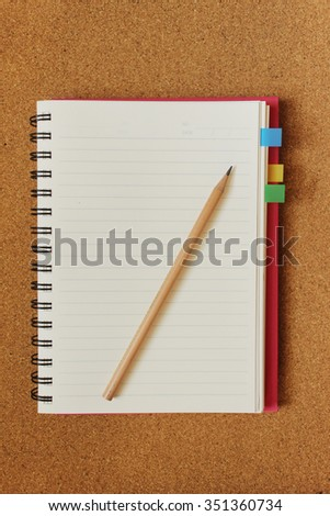 Blank page of pink line notebook with bookmark and pencil on cork board background - stock photo