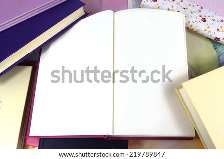 Blank pages in open book on background covered in books. Copy space.
