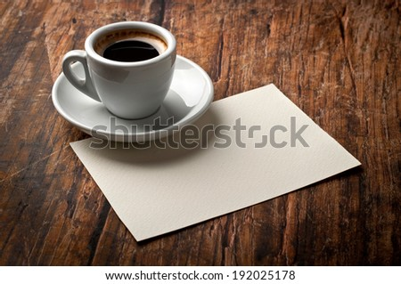 Blank paper and coffee cup on wood table