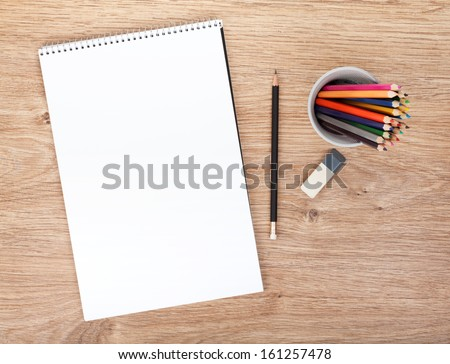 Blank paper and colorful pencils on the wooden table. View from above - stock photo
