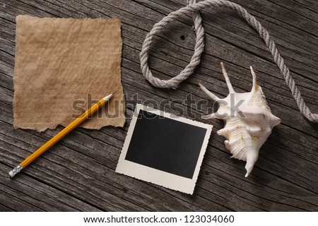 Blank paper and instant photo with pencil, shell, and string  on wooden background - stock photo