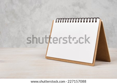 Blank paper calendar on wooden table - stock photo