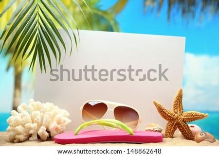 Blank paper card and seashells on sand beach. - stock photo