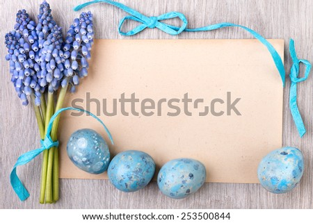 Blank paper card framed by blue ribbons, Easter eggs and grape hyacinth flowers, space for your text - stock photo