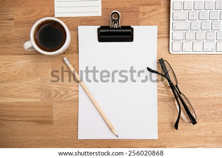 Blank paper, coffee, glasses and keyboard on the office table - stock photo