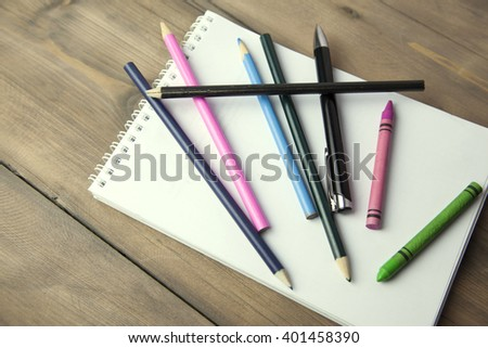 Blank paper, colorful pencils and pen on the wooden table