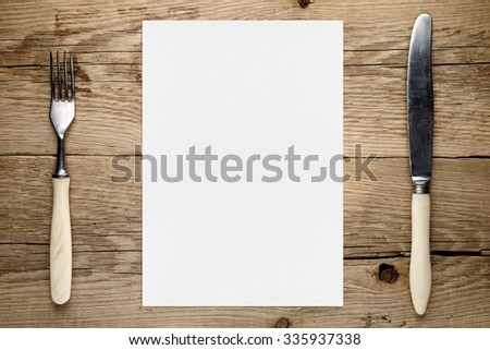 Blank paper for menu and fork and knife on wooden table - stock photo