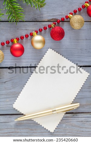 Blank paper for message with christmas decoration and fir on a wooden table. - stock photo