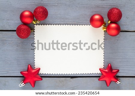 Blank paper for message with red christmas decoration on a wooden table. - stock photo