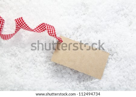 Blank paper gift tag or label with copyspace for your Christmas greeting in winter snow with a red and white checked decorative ribbon - stock photo