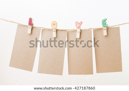 Blank paper hanging on love clothesline with white background - stock photo