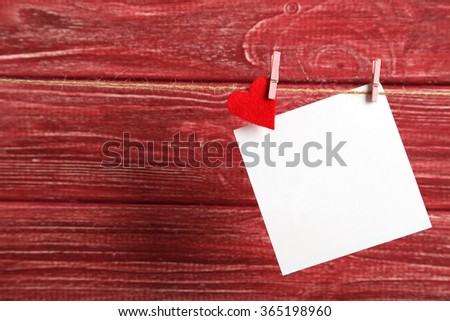 Blank paper hanging on rope on red wooden background - stock photo