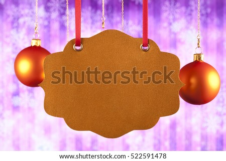 Blank paper label and Christmas baubles on abstract background