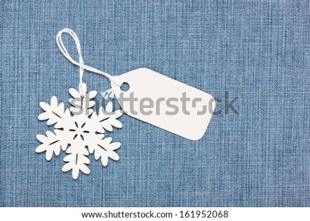 Blank paper label tag and snowflake on  blue jeans - stock photo