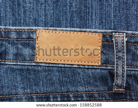 Blank paper label tag on  blue jeans - stock photo