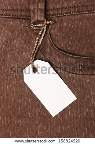 Blank paper label tag on brown jeans  - stock photo