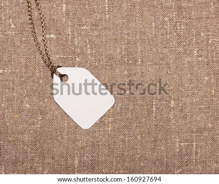Blank paper label tag on sackcloth - stock photo