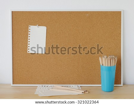 Blank paper on cork board and pencils on wood table over white cement wall background, template - stock photo