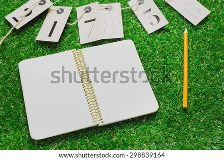Blank paper on grass - stock photo